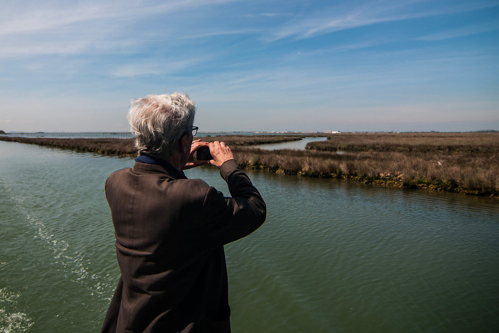 """VENICE, ITALY - APRIL 2018. <br /> A tourist takes a picture of the landscape of the Venetian lagoon while sailing along a canal close to Torcello Island during the fishing tour of the moeche. After visiting Emiliano's """"cason"""", the typical temporary house of the fishermen of the Venetian lagoon, the next stop will be in another """"cason"""", where they will taste some fresh cooked moeche."""