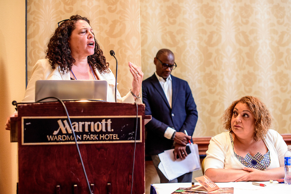 """Washington, D.C. - August 05, 2016: <br /> Lisa Garcia, Vice President of Healthy Communities at Earthjustice speaks during the Earthjustice hosted panel """"Environmental Justice 101"""" during the National Association of Black Journalists/National Association of Hispanic Journalists event Friday Aug. 5., 2016 from 2:45-4:15 pm at the Washington Marriott Wardman Park. <br /> Moderator, Darryl D. Fears, Reporter, The Washington Post stands in the background and Martha Dina Arguello, Executive Director of Physicians for Social Responsibility, listens on the right. <br /> <br /> Panelists are: Moderator, Darryl D. Fears, Reporter, The Washington Post, Martha Dina Arguello, Executive Director of Physicians for Social Responsibility, Dr. Beverly Wright, Executive director of Dillard University's Deep South Center for Environmental Justice, Dr. Robert Bullard, Dean of the School of Public Affairs at Texas Southern University, and Lisa Garcia, Vice President of Healthy Communities at Earthjustice.<br /> <br /> CREDIT: Matt Roth"""