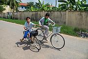 Twee kinderen fietsen door een buitenwijk van Phnom Penh.