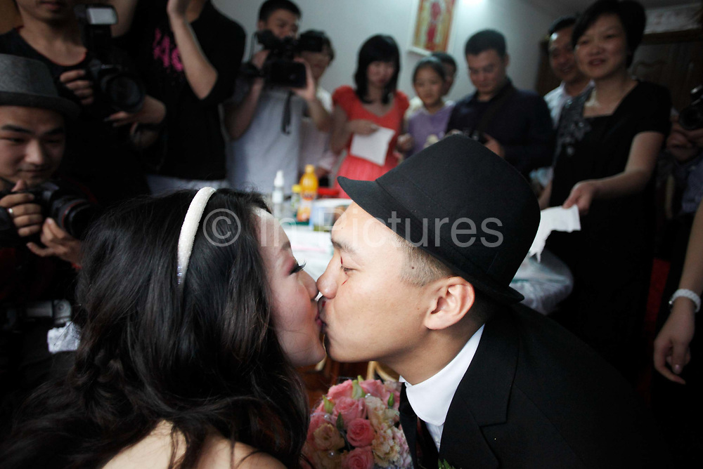Under the watchful eyes of rowdy relatives and friends, Coca Dai expresses his love for his bride, Juan Juan, and kisses her at her home in Shanghai, China on 23 May 2009. A hip street artist and a recent Catholic convert, Mr. Dai is one of many young Chinese embracing religion, perhaps to fill the lack of belief and ideology in an authoritarian communist China that embraces the most extreme form of capitalism in practice. The Chinese government and the Vatican have a long history of simmering mutual distrust and suspicion, as two parties compete for the control of the Chinese Catholic church, with some 15 million and growing number of faithfuls.  Overall Christians now number over 110 million in China, which makes it the third largest Christian nation in the world.