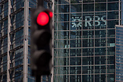 A red stop traffic light with the London headquarters of the Royal Bank of Scotland RBS on Bishopsgate, on 15th August 2016 in the City of London, UK.  The Royal Bank of Scotland is one of the retail banking subsidiaries of The Royal Bank of Scotland Group plc, and together with NatWest and Ulster Bank, provides banking facilities throughout the UK and Ireland with around 700 branches, mainly in Scotland though there are branches in many larger towns and cities throughout England and Wales.