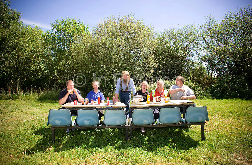 Jon the owner of Jacks burger van and some of his regular customers having lunch at a small rural roadside paddock off the A10 on the 21st May 2010 in Kings Lynn in the United Kingdom.