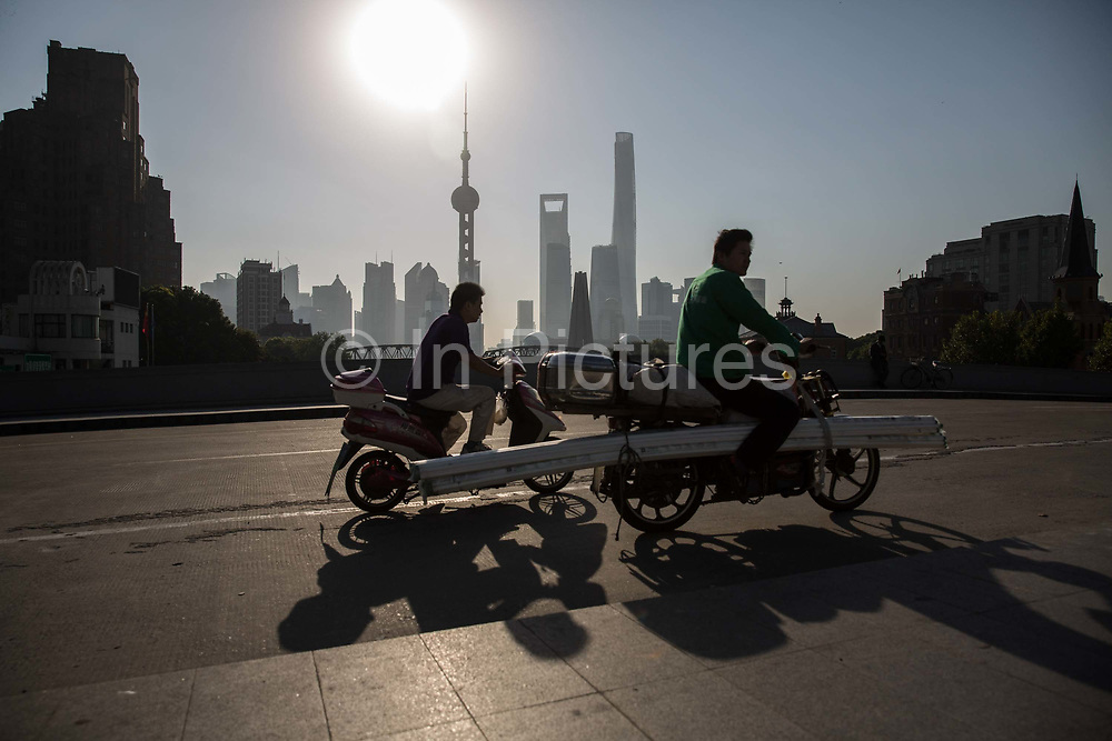 Commuters ride their bike across a bridge near the Bund while buildings of Pudongs Lujiazui financial district stand across the Huangpu River as the sun rises in Shanghai, China, on Friday, Oct. 2, 2015.