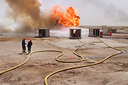 "Firefighters from the Kuwait Oil Company (called KWWK: Kuwait Wild Well Killers) connect hoses to water tanks and pumps by the second oil well fire they were working on in Iraq's Rumaila Oil field. Later in the day they failed to extinguished this fire with water and then tried to stop the flow of gas and oil with drilling mud using what is called a ""stinger,"" a tapered pipe on the end of a long steel boom controlled by a bulldozer. Drilling mud, under high pressure, is pumped through the stinger into the well, stopping the flow of oil and gas. This was also unsuccessful. The Rumaila field is one of Iraq's biggest oil fields with five billion barrels in reserve. Many of the wells are 10,000 feet deep and produce huge volumes of oil and gas under tremendous pressure, which makes capping them very difficult and dangerous. Rumaila is also spelled Rumeilah.."