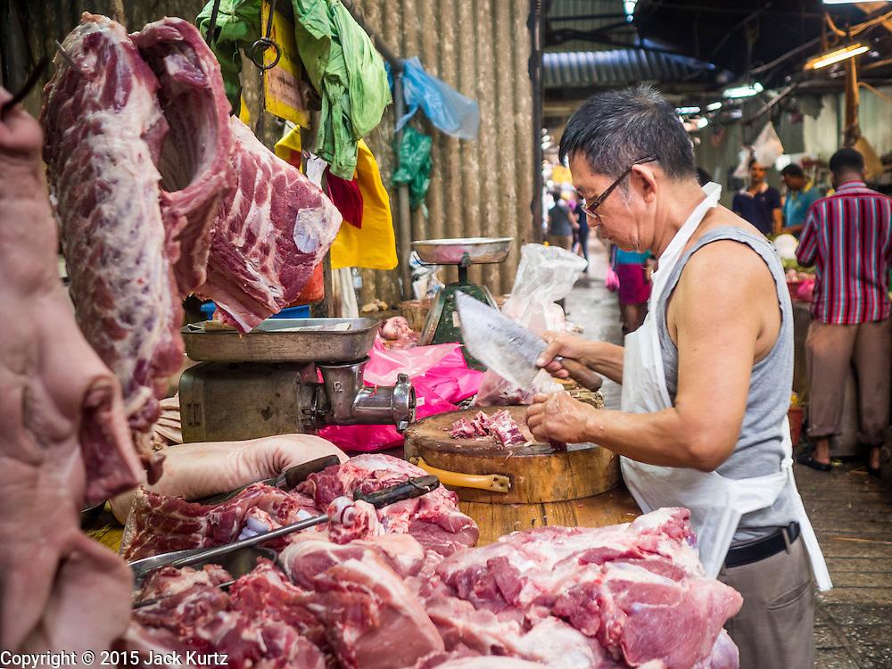 05 JUNE 2015 - KUALA LUMPUR, MALAYSIA: A butcher cuts up pork in a wet market near the Chinatown section of Kuala Lumpur.     PHOTO BY JACK KURTZ