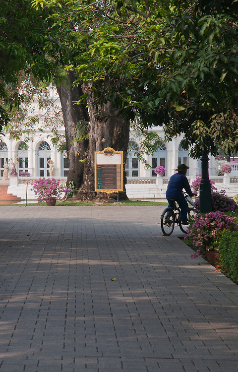 The gardener cycling past, working at the presidential summer palace, outskirts of Bangkok, Thailand.