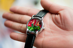 Detail of shopkeeper holding souvenir watch with Chairman Mao picture in a market in Beijing China