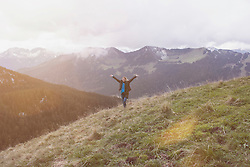 Young woman with arms raised standing in the mountain, Bavaria, Germany