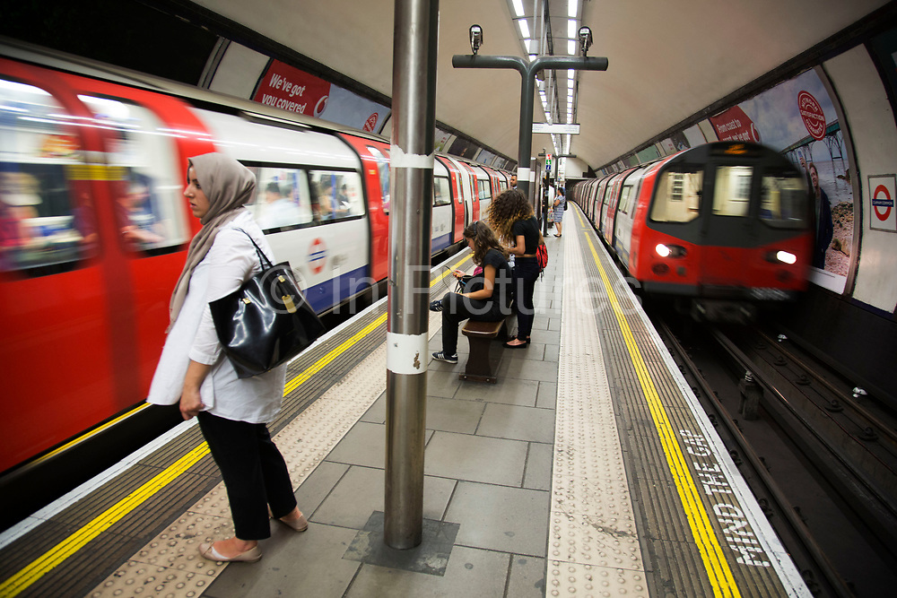 TfL underground trains come and go on the double platforms at Clapham Common tube station on the Northern Line in London, England, United Kingdom.