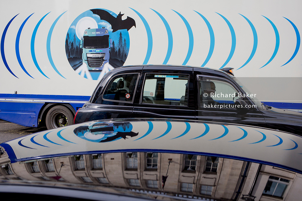 The design on the side of an HGV for the rehearsal studio company 'Fly By Nite' and a passing taxi cab in Great Marlborough Street, on 5th March 2019, in London, England.