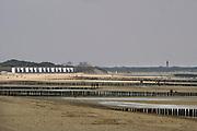 Nederland, Zeeland, Groede, 10-9-2019 Op het zeeuws vlaamse strand . Badhuisjes tegen de duinen, duinrand, cadzand bad in de verte . Palen in het zand als golfbreker .Foto: Flip Franssen