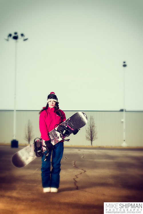 Adult female snowboarder poses in vacant parking lot. MR
