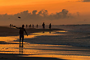 A man tosses a frisbee as people gather to watch the sunrise on the beach on a cloudy morning June 5, 2017 in Folly Beach, South Carolina. Folly Beach is a quirky beach community outside Charleston known to locals as the Edge of America.