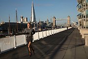 Runner takes his exercise along the river path along the River Thames near to Tower Bridge in Wapping in London, England, United Kingdom.