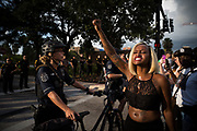 Loneisha Marchman raises a clenched fist to police officers during a Black Lives Matter protest, held in response to the deaths of Alton Sterling and Philando Castile, in Tampa, Florida, U.S., July 11, 2016.