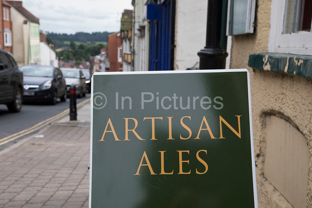 Sign for artisan ales. Ludlow is a market town in Shropshire, England. With a population of approximately 11,000, Ludlow is the largest town in south Shropshire. The town is near the confluence of two rivers. The oldest part is the medieval walled town, founded in the late 11th century after the Norman conquest of England. It is centred on a small hill which lies on the eastern bank of a bend of the River Teme. Atop this hill is Ludlow Castle and the parish church, St Laurences, the largest in the county. From there the streets slope downward to the River Teme.