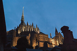 Twilight frames the medieval Mont Saint-Michel.  Sited on the borders both Brittany and Normandy, this  landmark has dominated its tidal island since the 11th century.  Pre-Romanesque in its styling, it has been a place of pilgrimage since its founding.