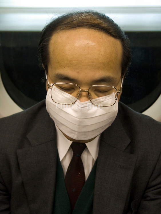 a middle aged businessman napping during his commute Japan