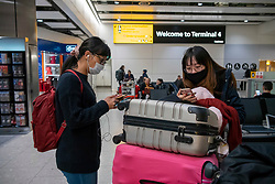 © Licensed to London News Pictures. 26/01/2020. London, UK. Two young women arrive with protective masks on at Heathrow Terminal 4 as signs have been installed around the terminal warning passengers of the symptoms of the new Wuhan coronavirus outbreak. The coronavirus virus has infected more than 10000 people across Asia in the past few weeks Photo credit: Alex Lentati/LNP