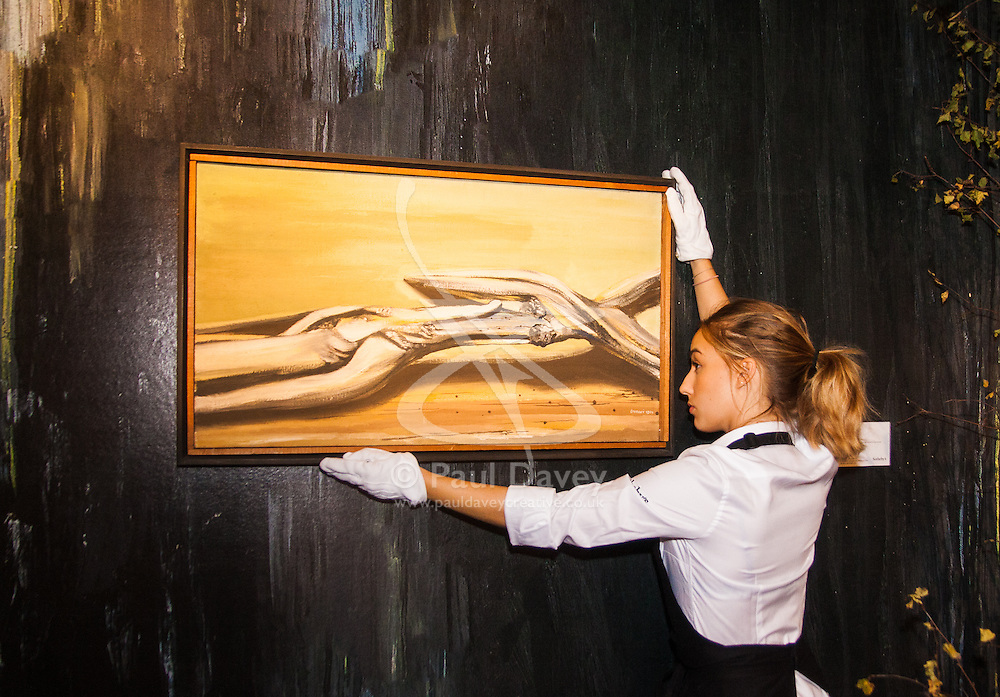 Sotheby's, Mayfair, London, November 7th 2014. Several outstanding examples of Czech avant-garde art from the Roy and Mary Cullen collection are to be auctioned by Sotheby's on November 12th. PICTURED: A Sotheby's worker puts the final touches to the pre-sale exhibition, straightening one of the key pieces, Roots, by Jindrich Styrsky which has an estimated value of £150,000 to £250,000 at auction.