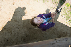 Girl climbing on rope in playground, Munich, Bavaria, Germany