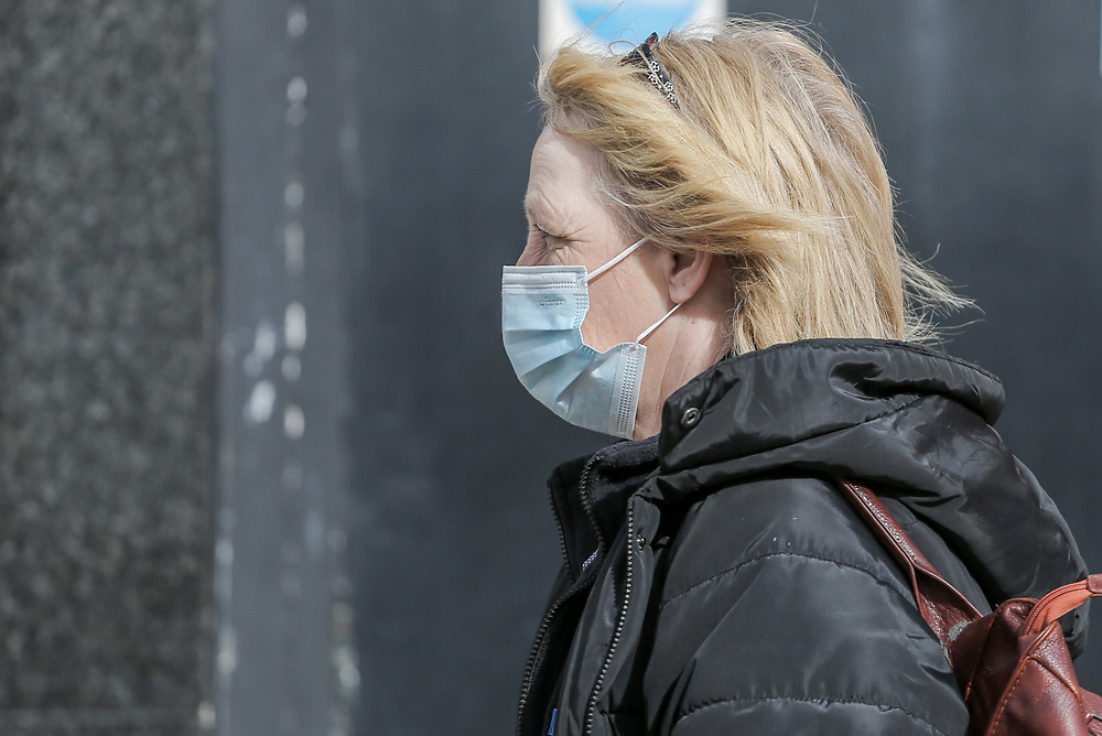 12th, March, 2021. Cheltenham, England. A member walks through the town centre wearing a mask.
