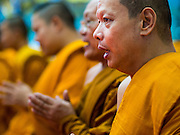 11 JANUARY 2015 - BANGKOK, THAILAND: Monks chant during a three day retreat to practice the Eight Precepts at Wat Dhamma Mongkol in Bangkok. Buddhist precepts are moral guidelines Buddhists follow rather than commandments in the Christian sense of the word. As Buddhists develop in the Dhamma, they find that the Precepts grounds their practice. One cannot waver and purposely break any of the Precepts. The Eight Precepts are typically also practiced during intensive meditation retreats of one day or longer. Wat Dhamma Mongkol, (pronounced 'Dhammamongkon') is on the edge of Bangkok, and visible from a number of places, especially from the elevated expressways around the city. The temple was started in the early 1960s by a revered monk who had spent more than 20 years in a forest retreat. The 95 meter high tower, completed in 1985, is a modern rendition of the tower that now marks the place of the Buddha's enlightenment in Bodhgaya, India. There are classrooms, a museum and meditation area inside the tower. The largest Buddha statue carved from a single piece of jade is on the temple grounds.   PHOTO BY JACK KURTZ