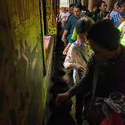 People donating money in the Temple of the Reclining Buddha, Bangkok, Thailand