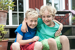 Friends young boys sitting steps house smiling