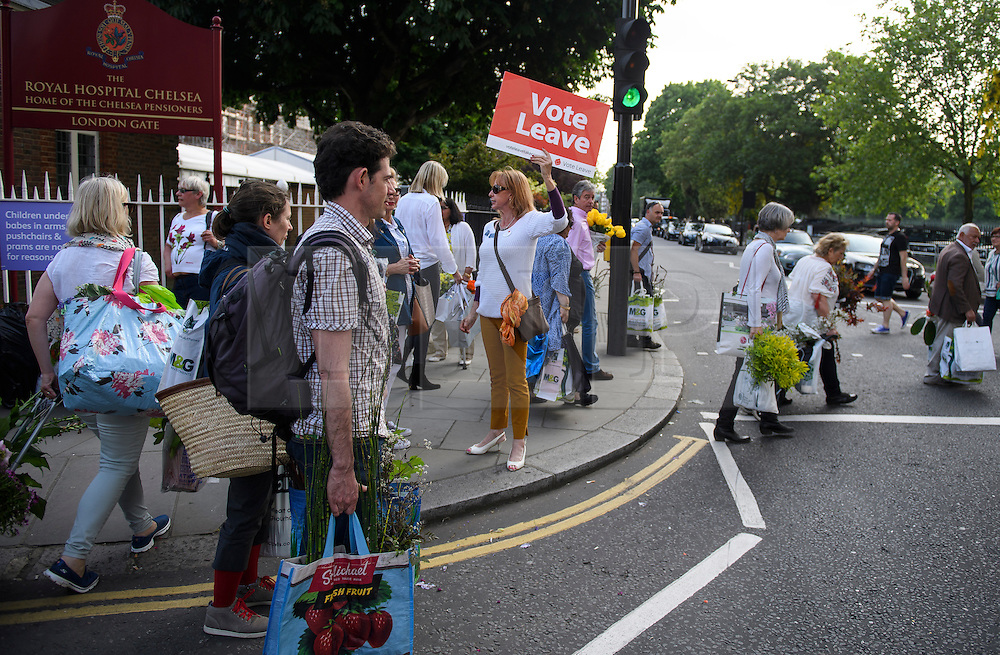 """© Licensed to London News Pictures. 28/05/2016. London, UK. A woman hold a """"VOTE LEAVE"""" Eu referendum sign as Members of the public carry exhibitors' plants from the 2016 Chelsea Flower show which ended today (Sat). A wide array of unusual and striking display items can be purchased on the closing day of The Royal Horticultural Society flagship flower show,  held at the Royal Hospital in Chelsea since 1913.  Photo credit: Ben Cawthra/LNP"""