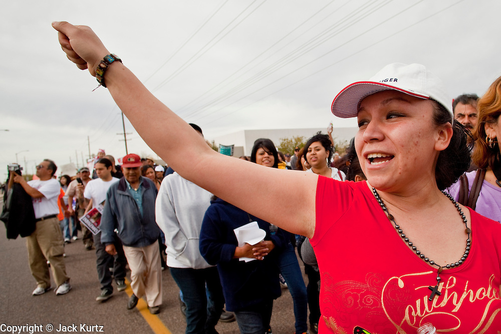 """16 JANUARY 2010 -- PHOENIX, AZ:  Iliana Guerrero (CQ) from Phoenx, jeers deputies lined up on Durango during the march. About 10,000 people marched the 2.5 miles from Falcon Park to the """"Tent City"""" on Durango to protest against Maricopa County Sheriff Joe Arpaio and his immigration enforcement tactics.   PHOTO BY JACK KURTZ"""