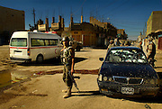 After shooting a fleeing insurgent's vehicle, members of the Iraqi army provide medical assistance to the car's occupants during an operation in Old Baqubah, Iraq, on March 11, 2007.