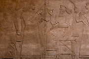 A detail from an ancient Assyrian stone carving 883-859 BC from Nimrud depicting a scene from the court of King Ashurnasirpal, in the British Museum, on 11th April 2018, in London, England. The detailed reliefs on display in Rooms 7-8 originally stood in the palace throne-room and in other royal apartments. They depict the king and his subjects engaged in a variety of activities. Ashurnasirpal is shown leading military campaigns against his enemies, engaging in ritual scenes with protective demons and hunting, a royal sport in ancient Mesopotamia.