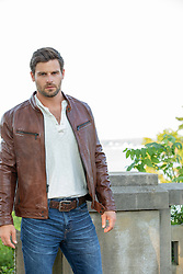 All American man with brown hair and blue eyes in a leather jacket