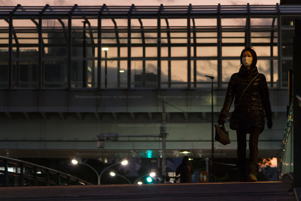 A Japanese woman , wearing a face mask against COVID-19 infection, walks in the street at dusk. Kachidoki, Tokyo, Japan. Wednesday February 3rd 2021