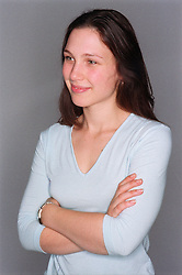 Portrait of teenage girl with arms crossed smiling,