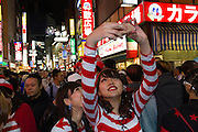 Two Japanese women, dressed as the character Waldo take a selfie with a smart phone during the Halloween celebrations in Shibuya, Tokyo, Japan. Saturday October 29th 2016 Halloween celebration in Japan have grown massively in the last few years. To ensure the safety of the crowds in Shibuya this year, the police closed several roads leading to the famous Hachiko Square, allowing costumed revellers to spread over a larger area.