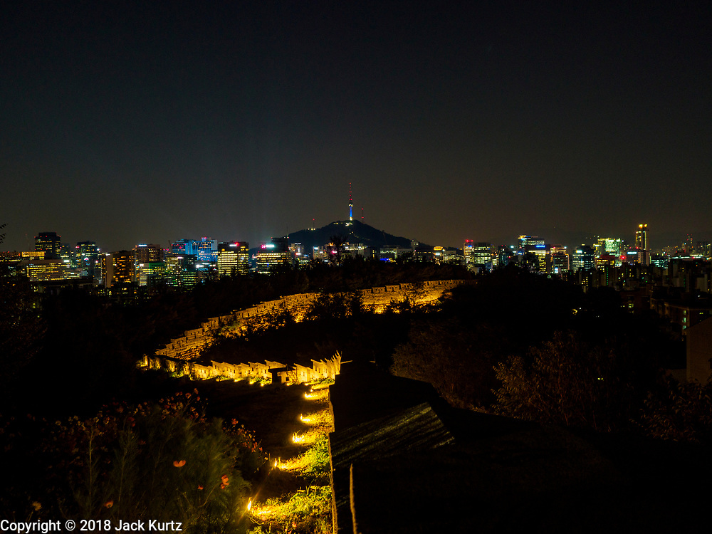 SEOUL, SOUTH KOREA: The city of Seoul, just after sunset, as seen from Samcheong Park, north of downtown, above the Gyeongbokgung Palace and Blue House. Seoul's ancient wall, that at one time protected the ancient city from invaders, is in the foreground.      PHOTO BY JACK KURTZ