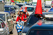08 MAY 2013 - BANGKOK, THAILAND: Red Shirts on a motorcycle hold up a photo of ousted and exiled Prime Minister Thaksin Shinawatra during a motorcade to the Thai parliament building. A splinter group of the Red Shirts, Thai supporters of exiled Prime Minister Thaksin Shinawatra, have besieged the Thai Constitutional Court for the last three weeks calling for the resignation of the justices, who have indicated they might oppose a proposed constitutional reform which would grant amnesty to people convicted of political crimes since 2007. This would probably include Thaksin. The justices have refused to step down. Wednesday the protesters moved their protest to the Thai Parliament, which is largely powerless to intervene.   PHOTO BY JACK KURTZ