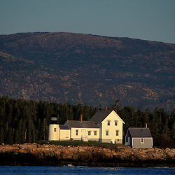 Winter Harbor, Acadia N.P., ME. Schoodic Peninsula. Lighthouse as seen from the Schoodic peninsula. Cadillac Mountain is in the background.