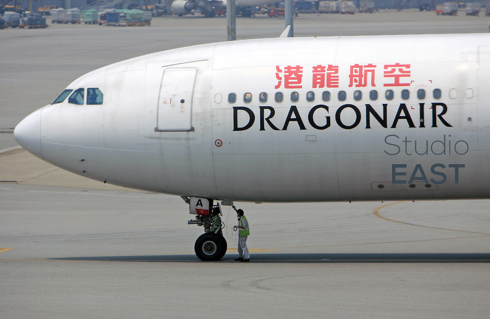 HONG KONG, HONG KONG - August 9: An airport ground staff attends a Dragon Air plane on the tarmac on August 9, 2006 in Hong Kong airport, China. (Photo by Lucas Schifres/Getty Images)