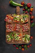 Pizza slices with shrimps, lettuce, tomato, tuna, and onions, on a wooden kitchen board, top view shot.