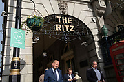 Londoners walk past a social distancing sign beneath the famous Ritz Hotel on Piccadilly during the second (Autumn) spike of the Coronavirus pandemic, on 5th October 2020, in London, England.