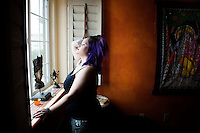 Woman awakening spiritually energetically in her window light. Bedroom series of sensual alchemist who likes to meditate and contemplate.