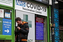 © Licensed to London News Pictures. 23/10/2021. London, UK. A man waits outside a Covid-19 vaccination centre for his jab in north London. Ministers are urging people o get a Covid-19 vaccine and booster jab as the experts, have reported a low uptake amid fears of further restrictions this winter as coronavirus cases rise. The Government is considering cutting the interval between booster jabs and the second dose of a Covid-19 vaccine from six month to five months. Photo credit: Dinendra Haria/LNP