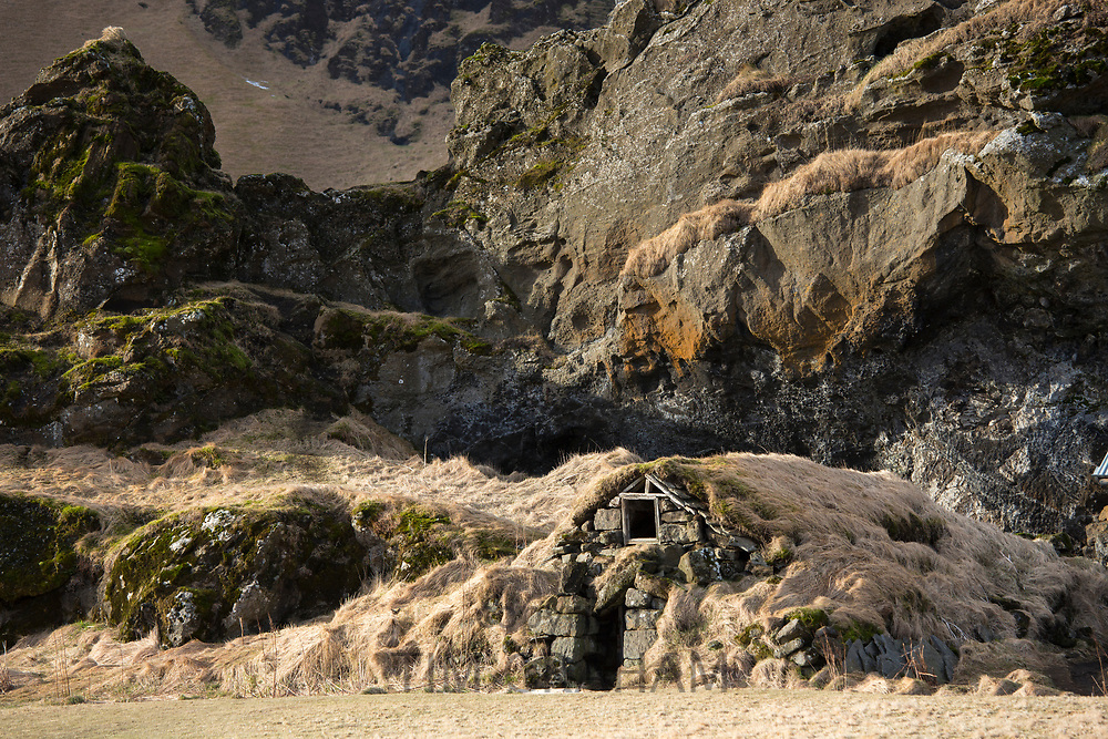 Ancient habitation turf house of Drangurinn underneath Drangshlío farm in foothills of Eyjafjöll. Folktale of a strongman ripping the giant boulder out of Hrútafell cliff.