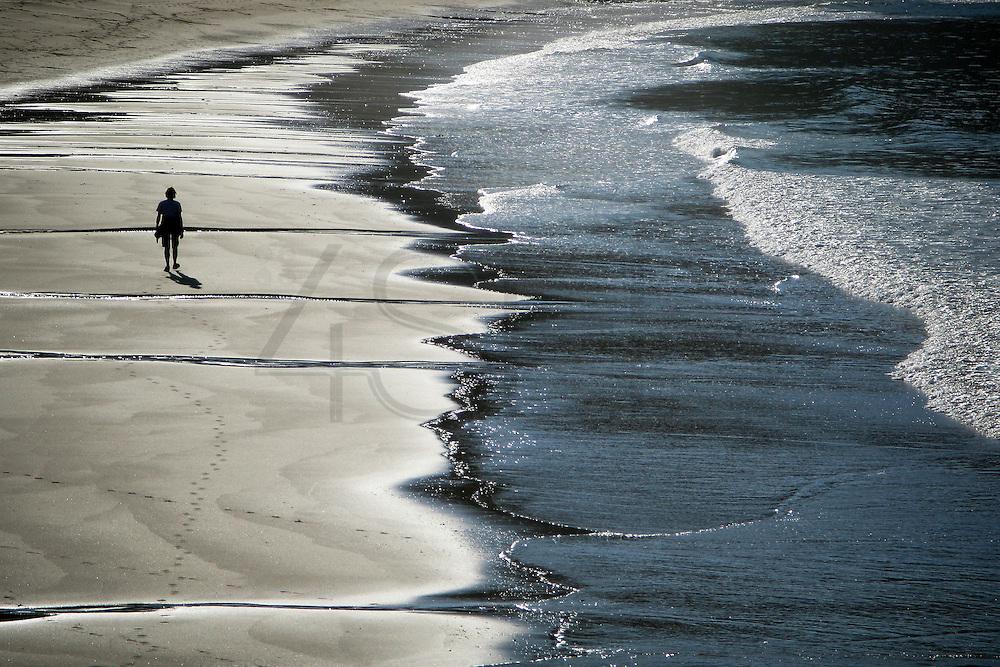 Portuguese Summer. A woman walks on the Praia da Luz beach in Algarve.