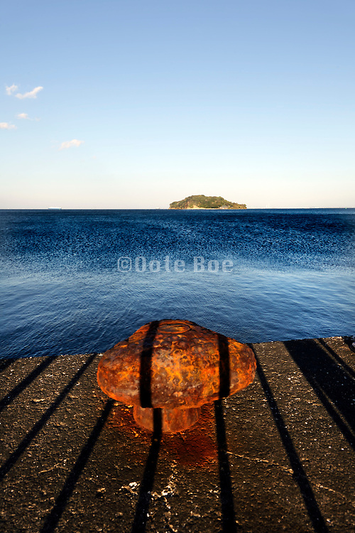 rusty bollard on fenced off pier with a little island in the distance Tokyo bay