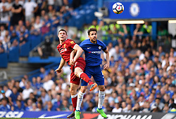 Chelsea's Cesc Fabregas (right) and Liverpool's James Milner battle for the ball during the Premier League match at Stamford Bridge, London.
