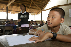 Unnamed teacher walks around class while student Tow (no age given) on a cold morning in the Grade 2 class which is made from bamboo and has no fixed walls.<br /> Viengpathana primary School,   Pha Oudom District, Bokeo Province, Lao PDR